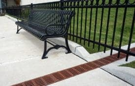 Neenah grates divert ground swale runoff across sidewalk